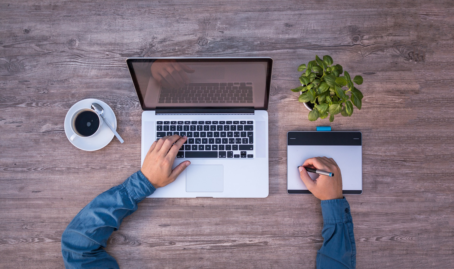 Designer using laptop and track pad with coffee